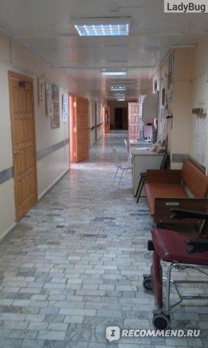 На диванчике справа сидят ожидающие регистрации, а за столами далее медсестра оформляет поступление