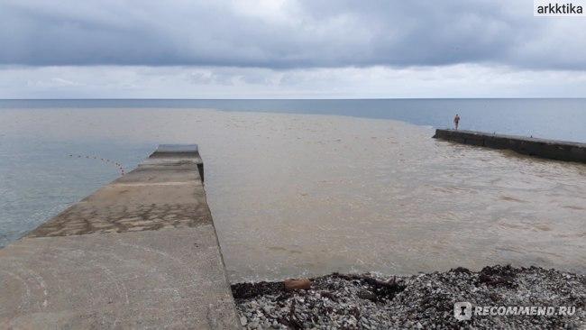 Грязная после дождя Агура впадает в море