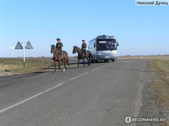 Очередной автобус с туристами в сопровождении казаков подходит к горе Сопатой