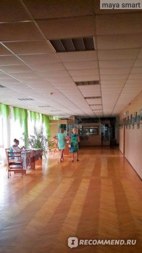 Знакомый коридор, ведущий в столовую, где время от времени появляется девушка-представитель турфирмы (сидит за столом).